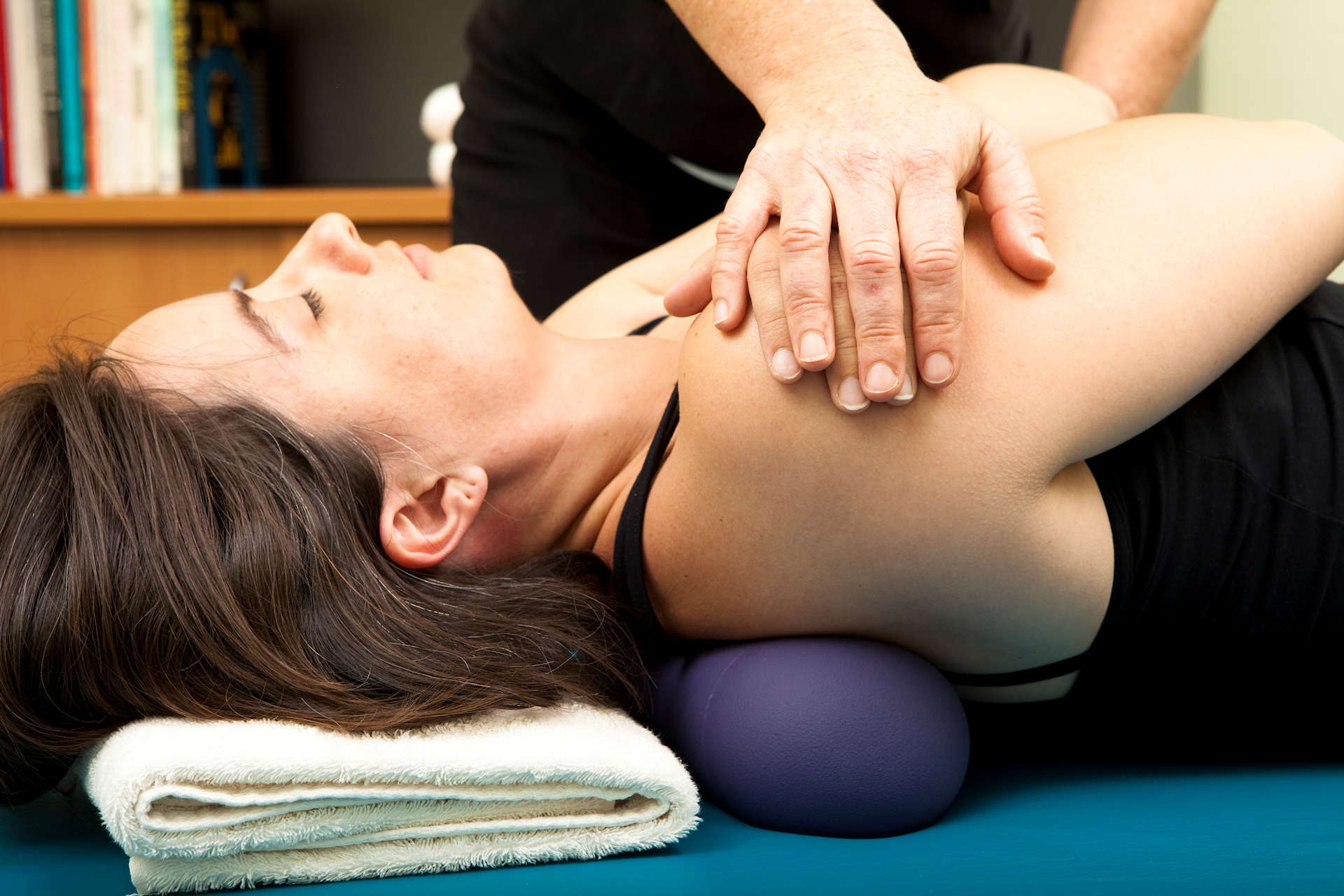woman receiving physiotherapy on her shoulder with gentle manipulation and her arms crossed lying on her back