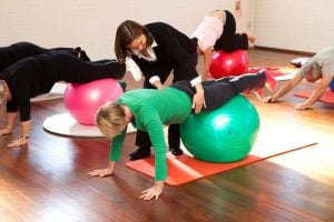 pilates on the ball group class in a hall getting individual assistance from physio Jodie Krantz