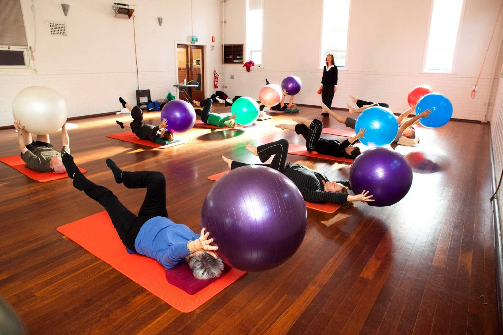pilates on the ball group class in a hall lying on their back doing the scissors exercise whilst holding the ball above their heads with physio Jodie Krantz instructing.