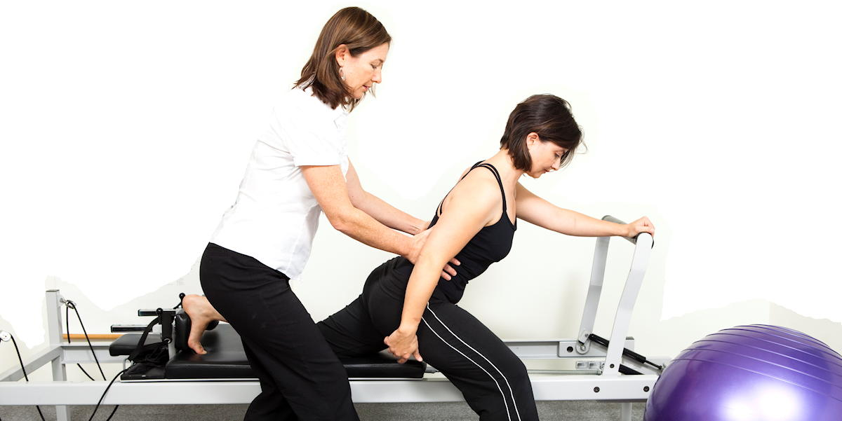 Physiotherapist Jodie Krantz instructing a woman on the Pilates reformer doing the scooter exercise
