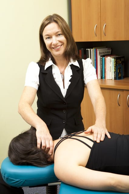 physiotherapist treating a patients neck whilst they are lying on a treatment table face down at Free2move Physiotherapy