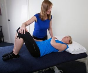 Female health practitioner treating woman who is lying on a table