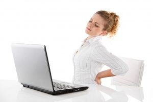 back pain - young woman in office with laptop
