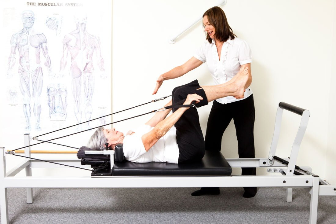 woman on a pilates reformer doing arm raises with legs in table top position being instructed by physiotherapist Jodie Krantz
