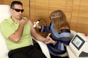 physiotherapist giving a man laser therapy