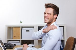 man working at desk with bad ergonomics holds shoulder in pain