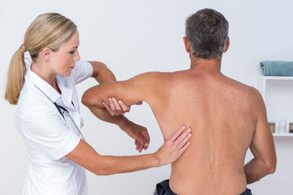 physiotherapist manipulating a mans shoulder