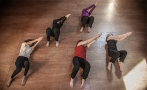 Group of people lying on the floor doing a Feldenkrais exercise in unison