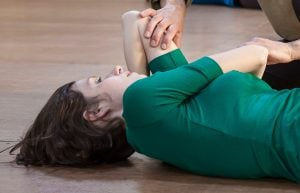 a woman lying on the floor with her elbow above her head getting assistnace from a Feldenkrais practitioner