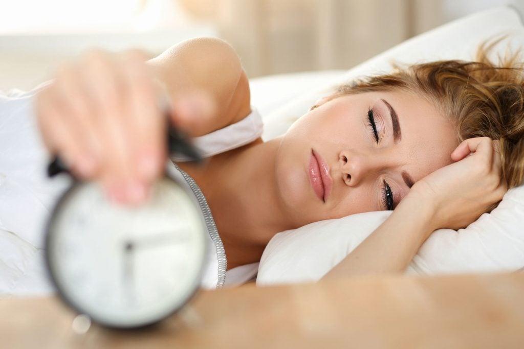 woman sleeping in, disabling alarm clock