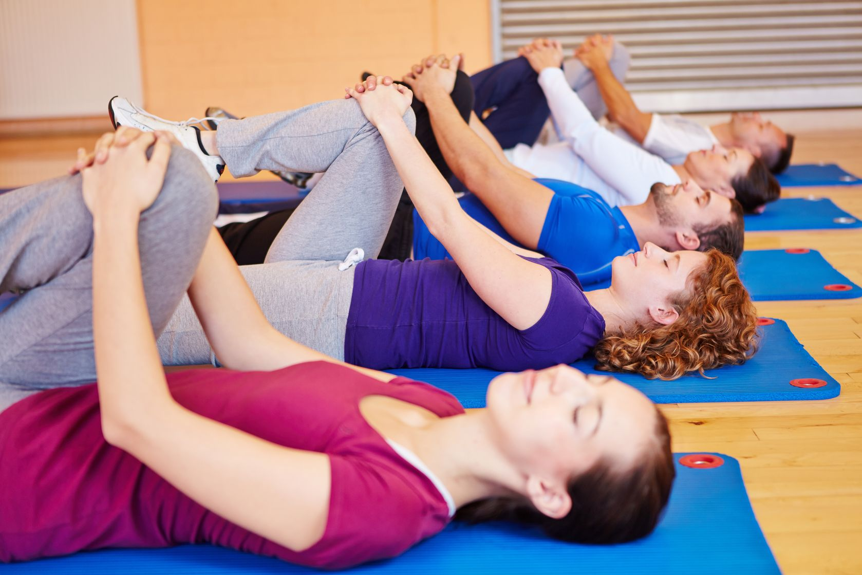 a group of 5 men and women laying on their backs holding one knee as part of a Feldenkrais exercise in a big room