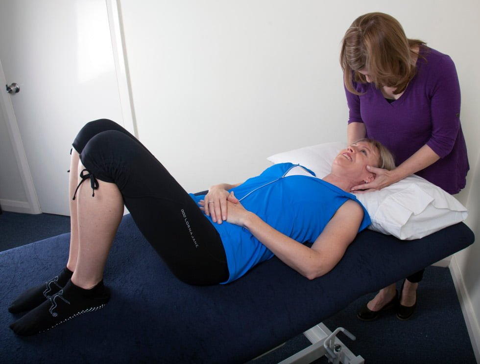 physiotherapist manipulating a woman's head and neck oin a table