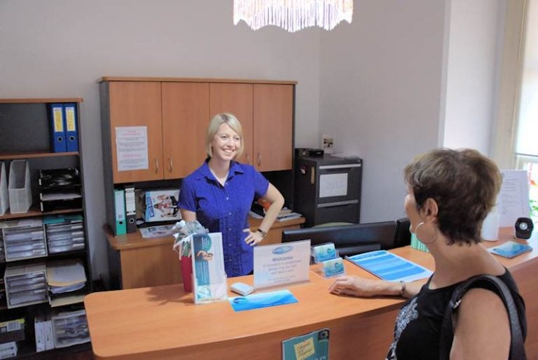 woman being served by staff behind the counter of Free2move Physiotherapy foyer