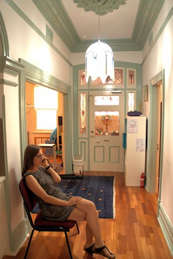 Jodie Krantz sitting in the hallway of Free2move Physiotherapy practise at 150 Vincent St North Perth