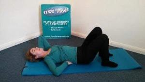 Jodie Krantz on the floor of Free2move pilates studio lying on her back one hand behind her head the other under her pelvis.