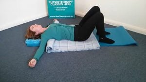 Jodie Krantz on her back on a rolled up blanket under her back and head cushion in the Free2move pilates studio feet on the ground arms out wide