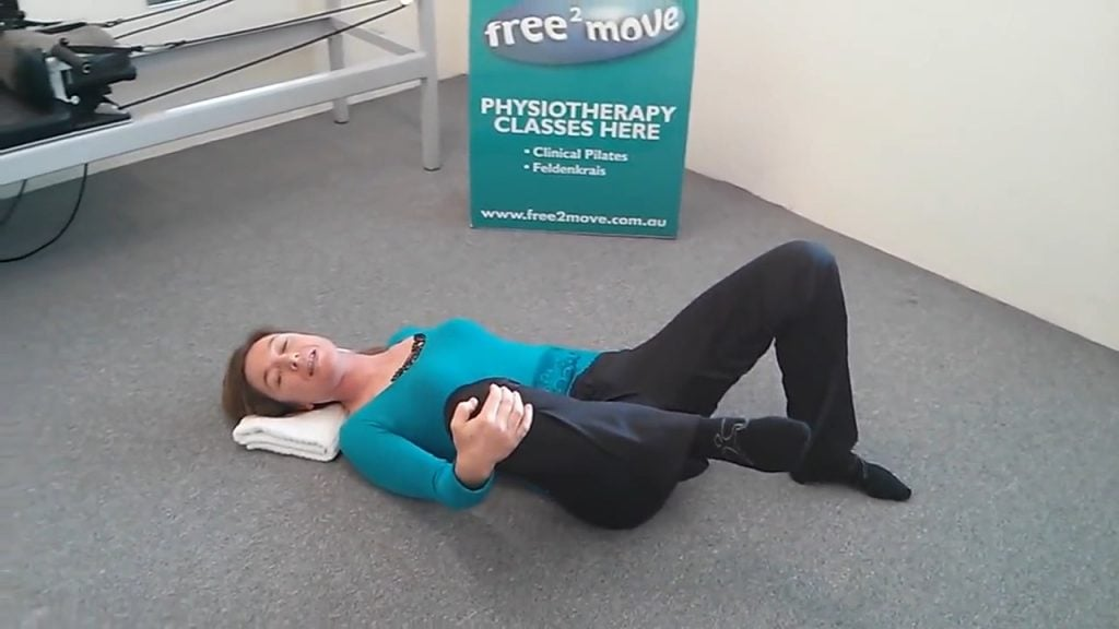 Jodie Krantz on the floor of Free2move Pilates studio on her back holding one knee and the other foot flat on the ground showing a hip freeing exercise.