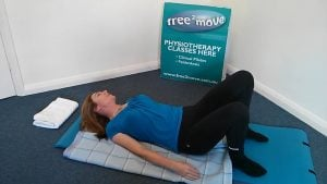 Jodie Krantz lying on a blanket with arms by her side and neck to one side in the Feldenkrais studio at Free2move