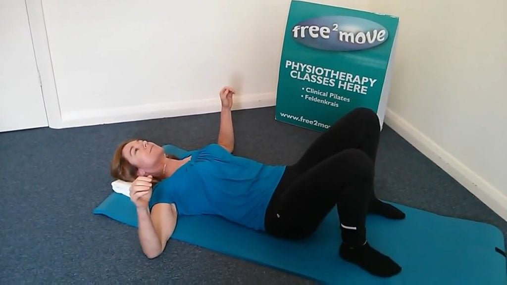 Jodie Krantz on the floor of Free2move pilates studio on her back with her hands lifted showing a way to release shoulder tension.