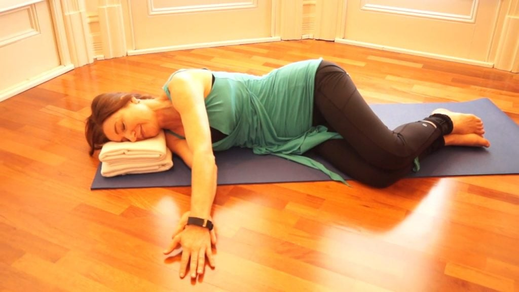Jodie Krantz lying on her side on a mat with one arm out to the side and the other sliding along top of if in the Feldenkrais studio at Free2move