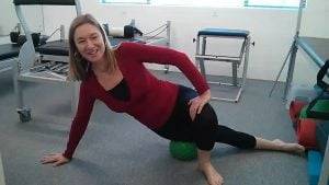 woman massaging itb with mini-ball in a pilates studio