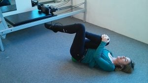 Jodie Krantz in the Free2move pilates studio stretching the hip flexor with one knee up and a mini-ball under the pelvis
