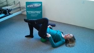 Jodie Krantz in a pilates studio doing a pelvic stability exercise with a mini-ball