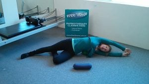 Jodie Krantz in the Free2move Pilates studio doing a side stretch with a mini-ball under her hip