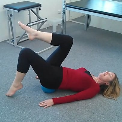 Jodie Krantz on the floor of the Free2move pilates studio doing the toe touching exercise with a mini-ball under her pelvis