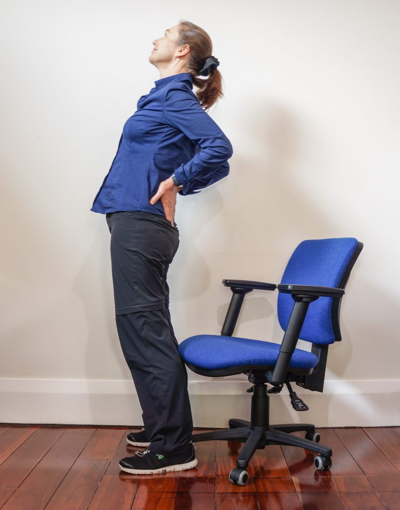 woman standing up from chair and doing a back bend exercise