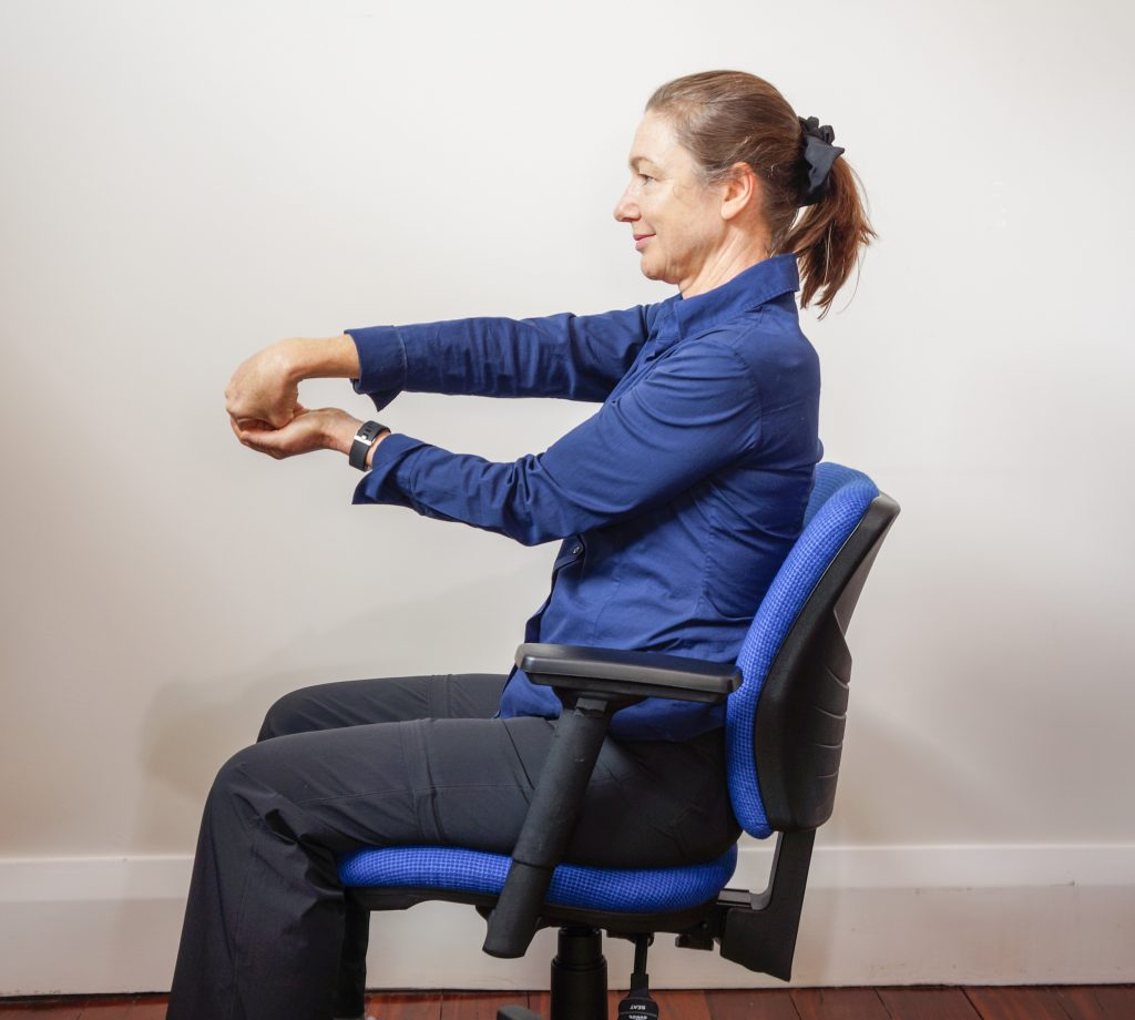 woman sitting in office chair with arms out front doing a forearm stretch