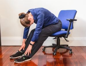 woman sitting on an office chair bending forward and touching her ankles