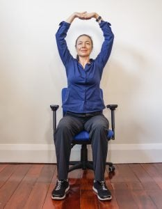 woman sitting on an office chair with her hands interleaved over her head stretching
