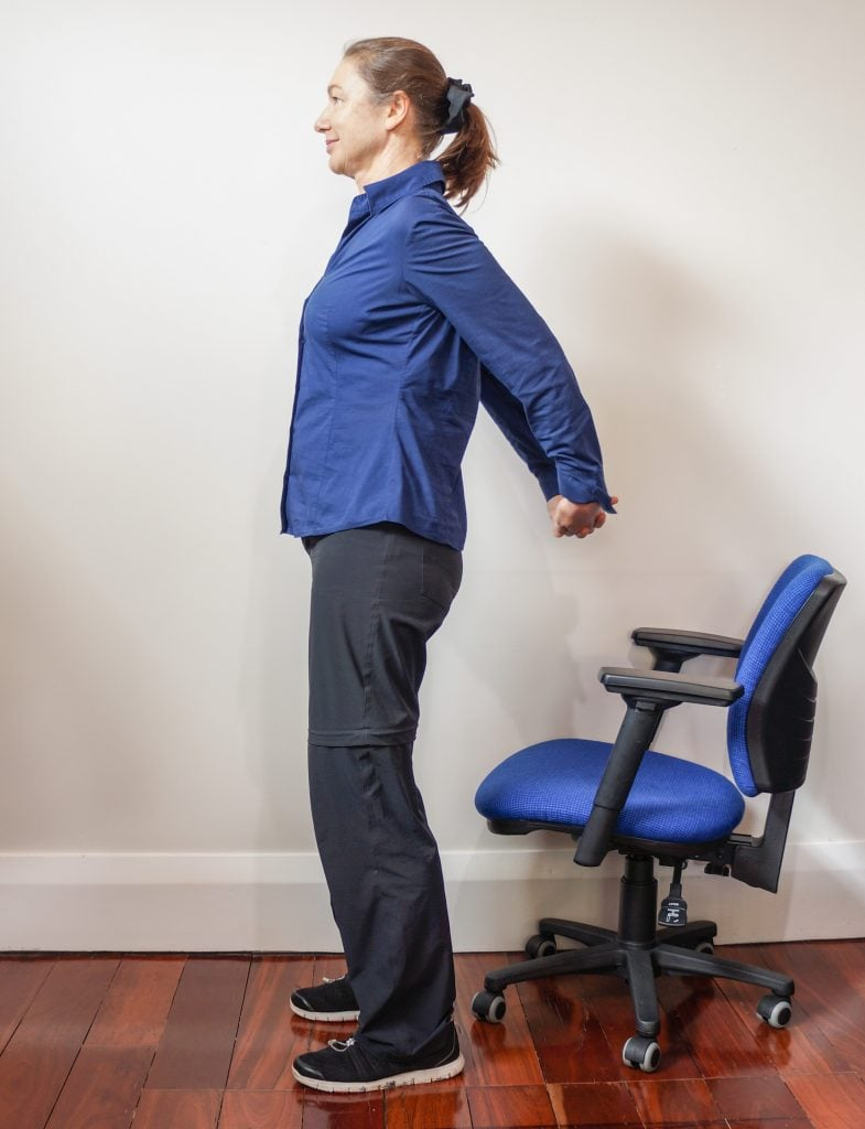 woman tanding near office chair with hands interleaved behind her back doing a pectoral stretch