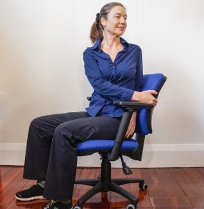woman sitting in office chair wisting round to the left looking behind