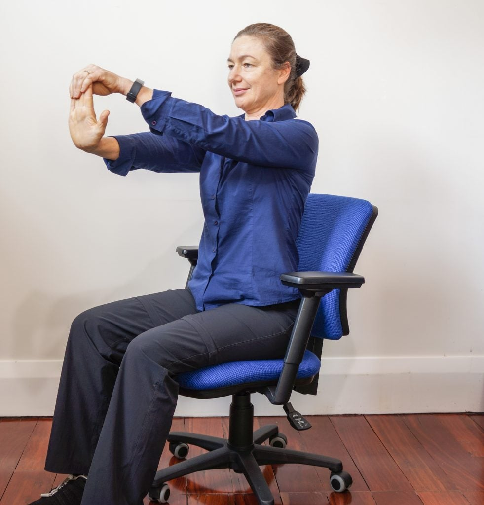 woman sitting on office chair with her hands out in front doing the stop sign stretch