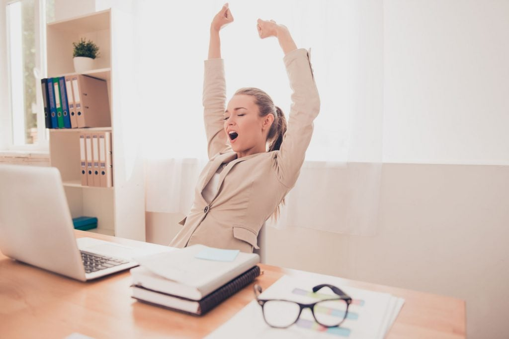 businesswoman stretching after prolonged sitting at her computer and doing breathing exercises