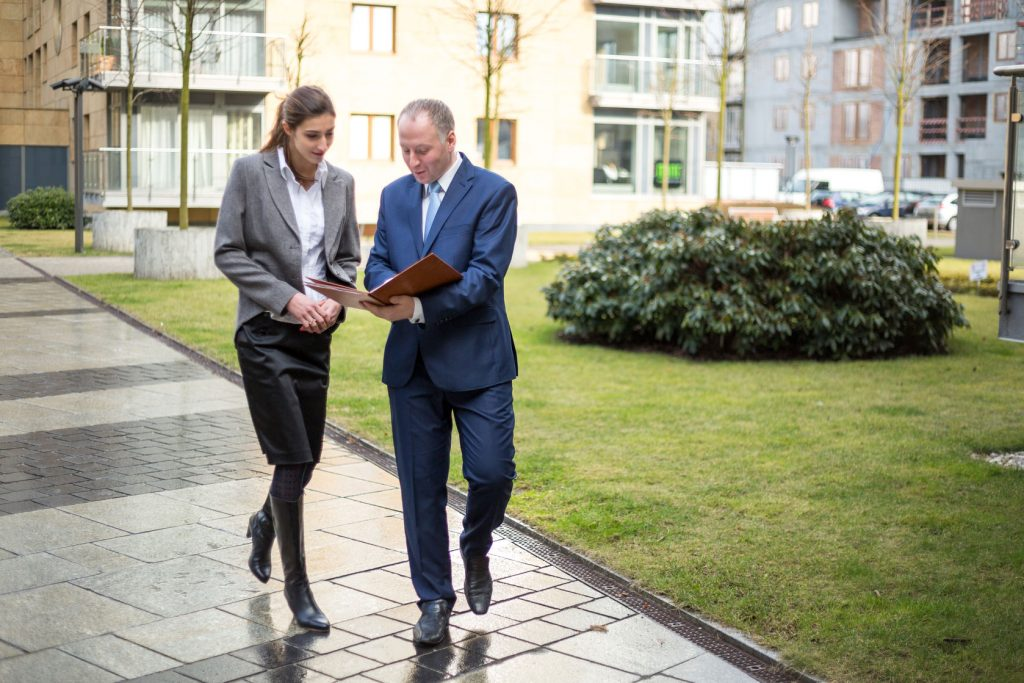 A business man and woman have a walking meeting and discussion while looking at a diary outside an office building next to a garden