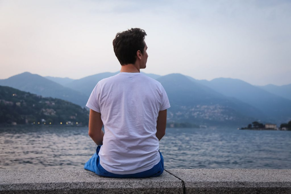 Man sitting on a wall near the ocean contemplating